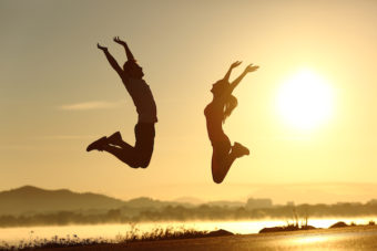 Happy couple jumping at the sunset
